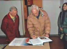 Alcuni visitatori firmano il registro delle presenze.